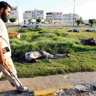 Kapinallinen kävelee surmattujen mustaihoisten ohitse Tripolissa elokuussa 2011.