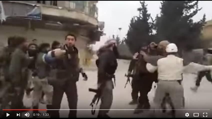 Näyttökuva videolta 1. Kuvan oikeassa laidassa White Helmetsin kypärää pitävä henkilö on lyömässä vankia.