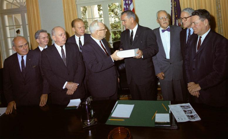 Warrenin komission jäsenet esittelevät raporttinsa presidentti Kennedyn salamurhasta presidentti Lyndon Johnsonille. Vasemmalta oikealle: Maailmanpankin entinen pääjohtaja John McCloy, J. Lee Rankin (komission päälakimies), senaattori Richard Russell, edustajainhuoneen jäsen Gerald Ford, korkeimman oikeuden puheenjohtaja Earl Warren (puheenjohtaja), presidentti Lyndon B. Johnson, (Kennedyn erottama) entinen CIA:n pääjohtaja Allen Dulles, senaattori John Sherman Cooper ja edustajainhuoneen jäsen Hale Boggs.